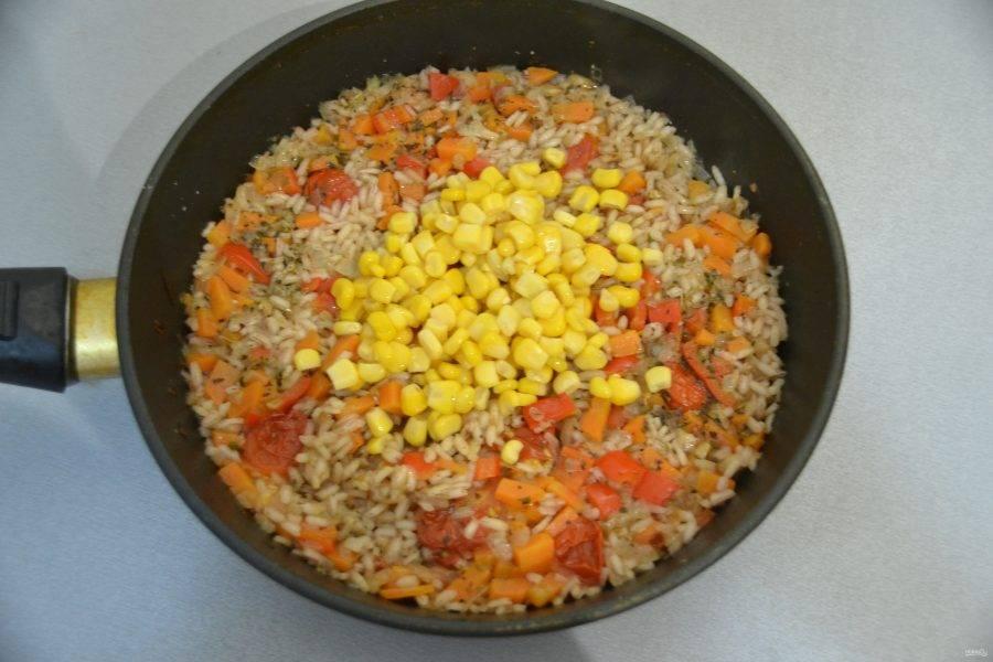 Добавьте к рису консервированную кукурузу и перемешайте, вместо кукурузы можно добавить консервированный горошек.