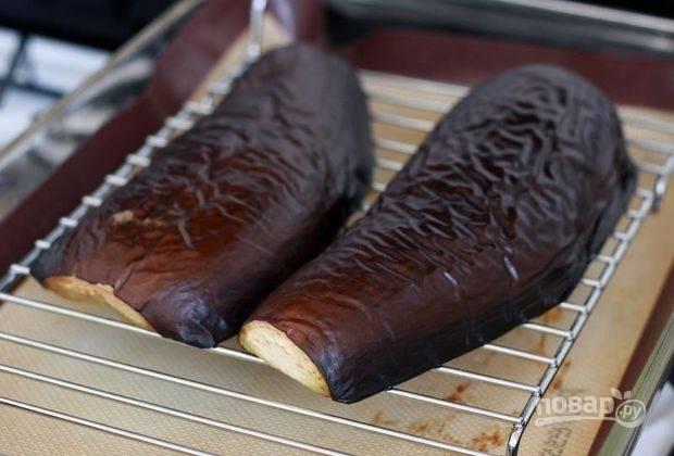 Баклажан помойте. Выложите его половинки на противень с маслом. Запекайте овощ в течение 20 минут при 200 градусах в духовке.