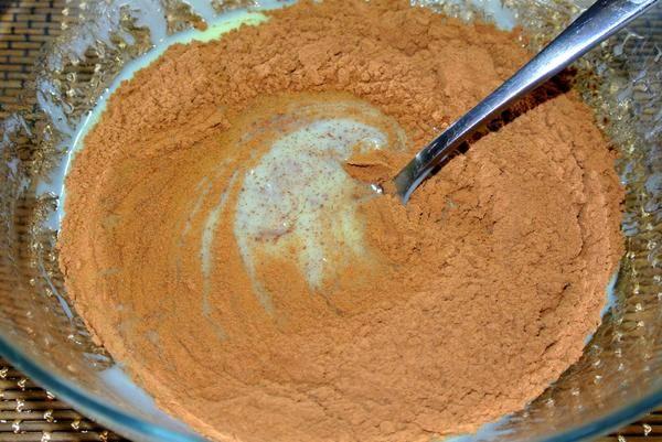 Дайте немного остыть подогретой смеси. После постепенно высыпайте какао, помешивая при этом смесь ложкой.
