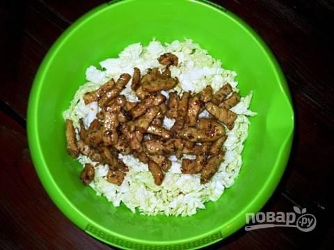 Тонко нарезаем пекинскую капусту и добавляем к ней жареное, чуть остывшее мясо.