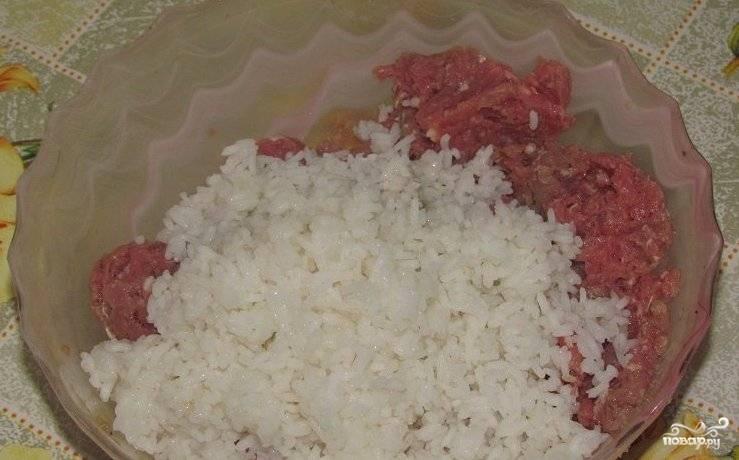 Для начала нам необходимо отварить рис, поэтому тщательно промываем его несколько раз, а затем ставим вариться на медленном огне. Когда рис будет на половину готов, выключаем огонь, сливаем с него воду и ждем, пока он немного остынет. Затем промываем его и смешиваем с мясным фаршем.