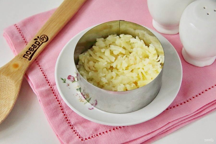 Салат выкладывайте на плоскую тарелку при помощи круглых кулинарных колец разного диаметра. Все слои необходимо посолить по вкусу и смазать майонезом. Поставьте большее по диаметру кольцо и выложите первым слоем тертый на крупной терке отварной картофель.