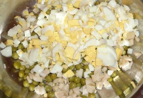 Сваренные вкрутую яйца мелко нарезаем. Добавляем к горошку и кальмарам.