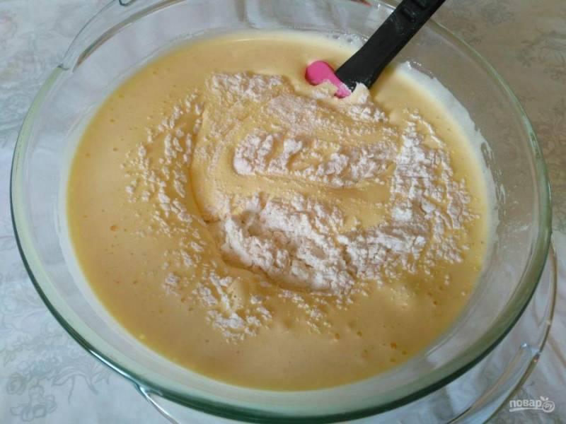 Муку соедините с разрыхлителем и просейте, частями всыпая её во взбитые с сахаром яйца. Перемешивайте бисквитную массу аккуратно, снизу вверх. Делать это удобно небольшой силиконовой лопаткой.