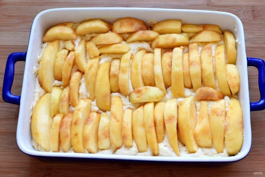 Яблоки очистить и нарезать крупными дольками. Выложить поверх теста черепицей, слегка вдавливая в тесто.