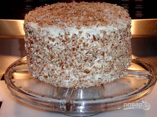 Теперь верх и бока торта нужно обсыпать кокосовой стружкой и ореховой крошкой, прижимая их немного к крему. Оставьте торт в холодильнике часов на 6, чтобы он пропитался.