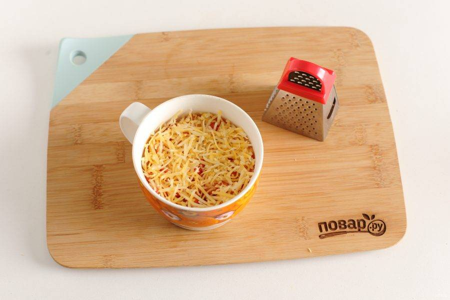 Посыпьте все тертым сыром и запекайте в микроволновке 2 минуты при мощности 950 Вт.