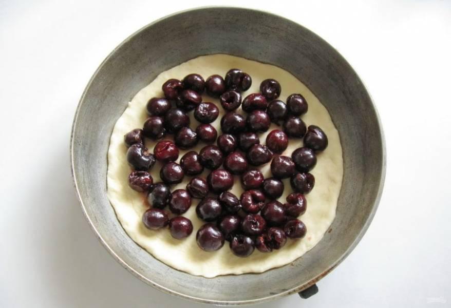 Достаньте тесто из миски, обомните и разделите на две части. Одну часть раскатайте в пласт и выложите в сковороду или любую форму для выпечки. Черешню помойте, удалите косточки. Выложите ровным слоем на тесто.