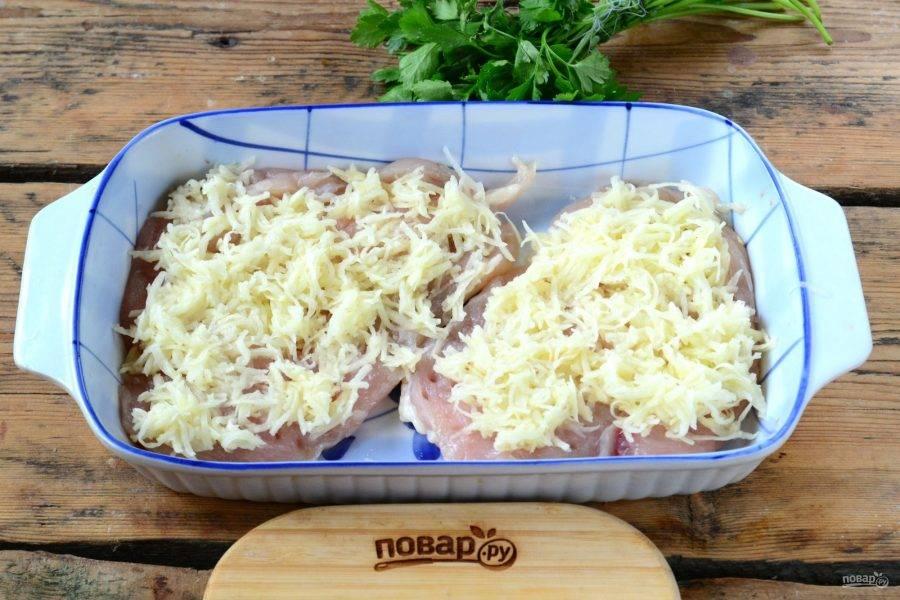 Картофель натрите на мелкой терке и выложите его на куриные грудки ровным слоем.