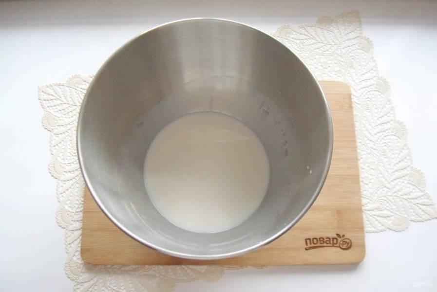 В глубокую миску или чашу планетарного миксера налейте теплое молоко. Добавьте дрожжи и сахар, перемешайте.