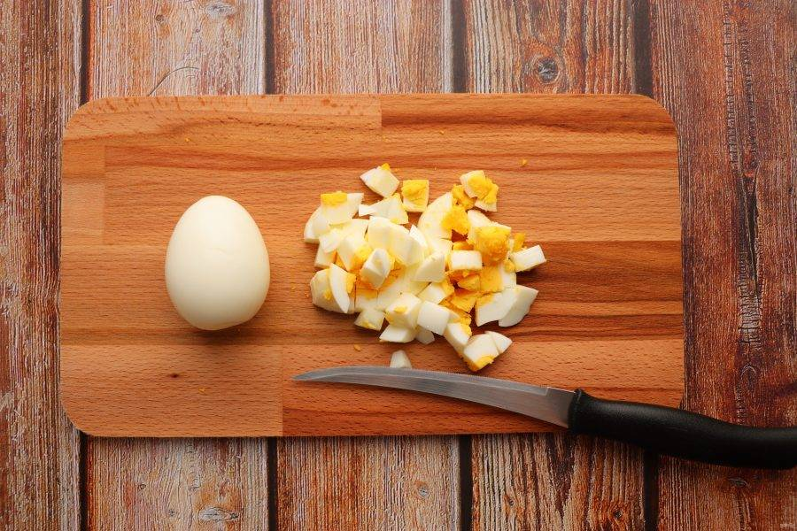 Яйца сварите вкрутую, очистите и нарежьте кубиками.