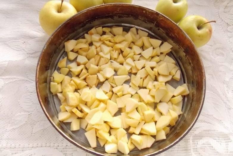 На дно разъемной формы для выпечки кладем пергамент, смазанный маслом. Сверху засыпаем яблоки.