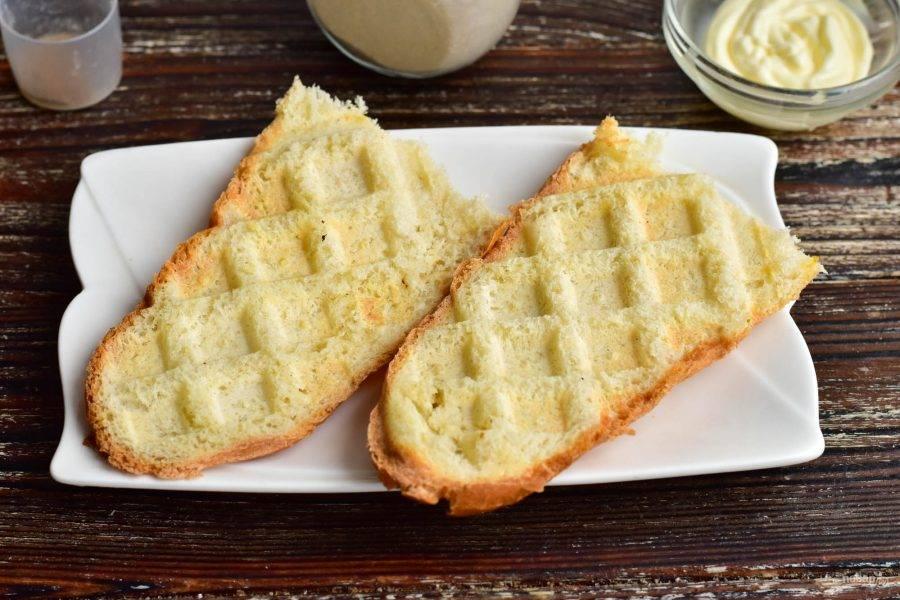 Минибагет разрежьте пополам, а затем вдоль пополам. Обжарьте его в вафельнице или на сковороде.