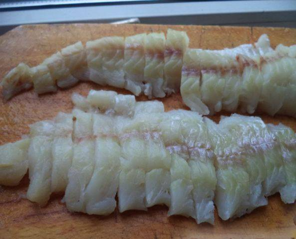 5. Рыбу для этого пирога можно брать любую без костей. Лучше всего подойдет филе. Его нужно нарезать на кусочки среднего размера.