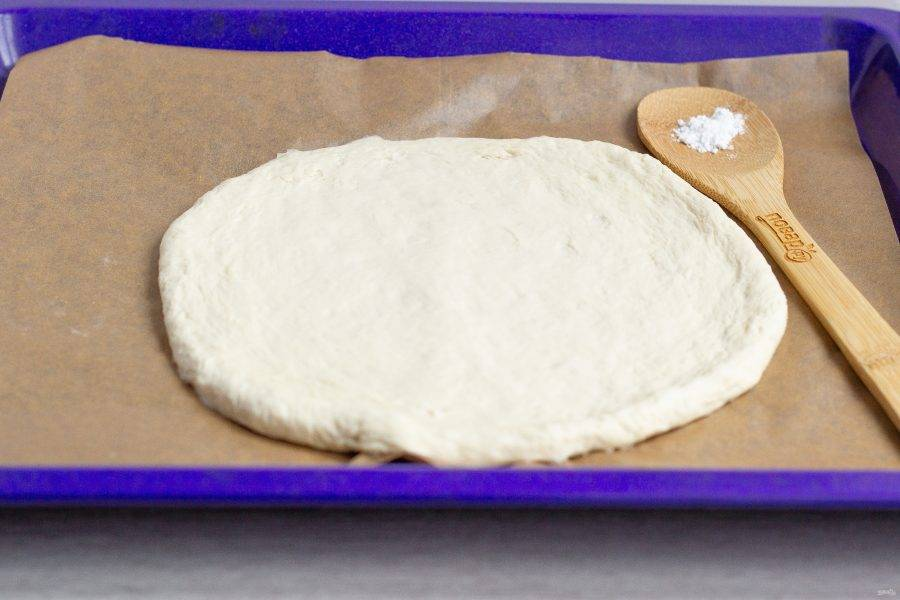 Тесто разделите на 2 неравные части: 2/3 и 1/3. Большую часть раскатайте в круг.