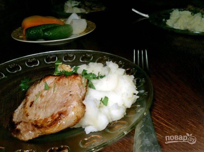 Вымойте петрушку, измельчите зелень острым ножом. Выложите на тарелку кусок поджаренной свинины и пару ложек картофельного пюре, посыпьте его зеленью. Подавайте блюдо к столу!