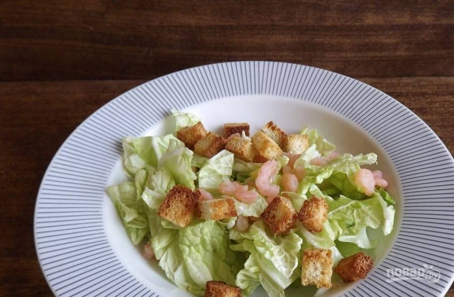 Салат вымойте и обсушите. Его листья порвите руками и выложите на тарелку. Добавьте к зелени отварные и очищенные и хлебные гренки, оставив немного для украшения салата.