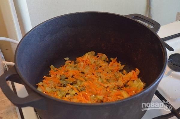 4. Разогрейте казан с небольшим количеством масла. Выложите лук с морковью и чесноком, обжарьте 3-5 минут, помешивая.