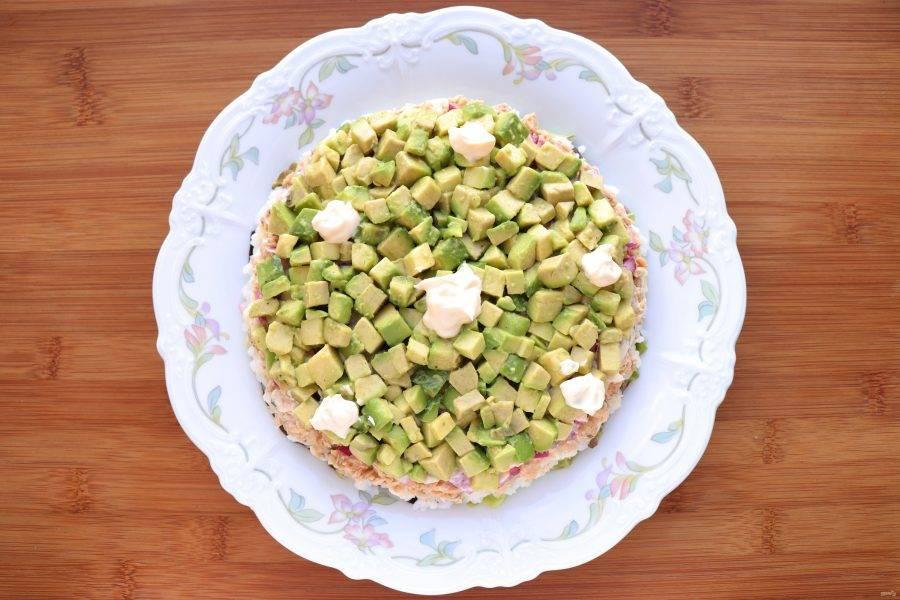 На лук выложите слой авокадо, посолите и поперчите по вкусу, промажьте майонезом.
