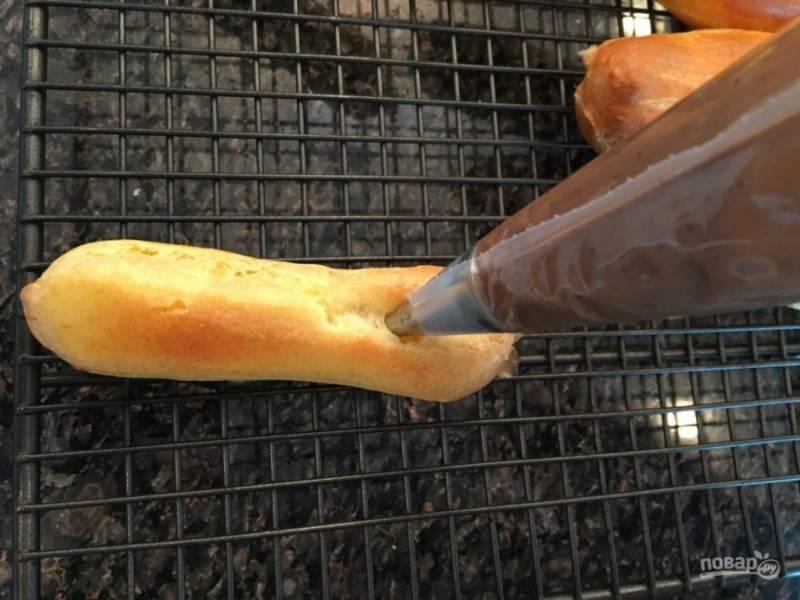 18.Готовый крем выложите в кондитерский мешок и с помощью отверстий, что сделали ранее, начините им пирожные.