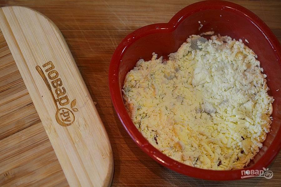 Первым слоем выложите тертые яичные желтки.