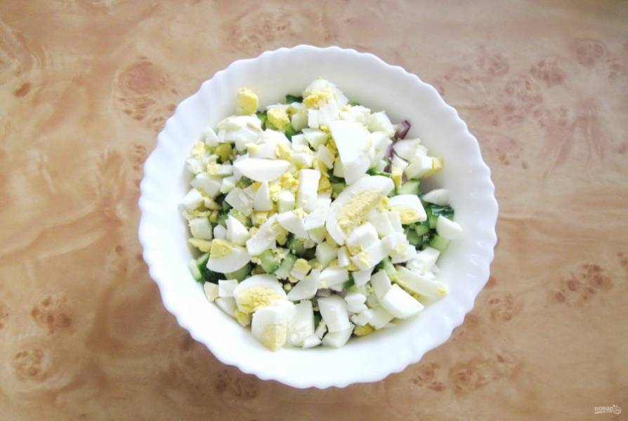 Яйца сварите вкрутую, охладите, очистите и мелко нарежьте. Выложите в салат.