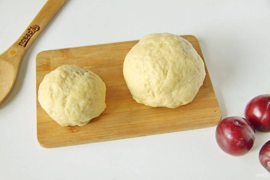Разделите тесто на две части. Одну часть, что чуть поменьше, поместите в морозилку. Другую распределите руками в смазанной маслом форме для выпечки, сформировав высокие бортики.