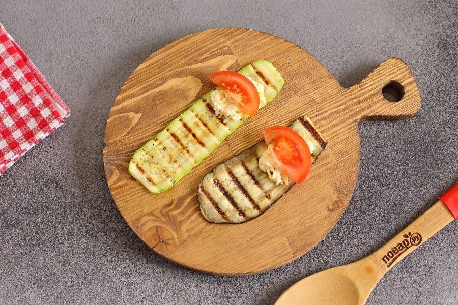 На основание обжаренных овощей выложите немного сырной начинки. Сверху выложите по дольке помидора.