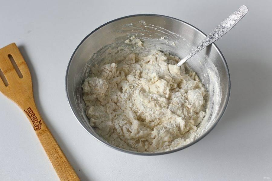 Перемешайте и частями введите муку. Перемешивайте тесто сначала ложкой, а затем, когда трудно станет мешать, продолжите замес руками на столе.