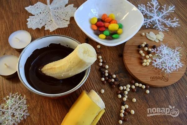 Растопите шоколад на водяной бане. Дайте немного остыть, чтобы шоколад не растекался по банану. Очистите бананы, разрежьте на две половинки. Окуните острым кончиком в шоколад, дайте немного застыть, поставьте срезом на тарелку, нанесите растопленный шоколад на место для ног пингвина.
