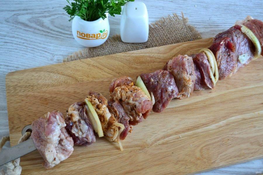Когда угли на мангале будут готовы, нанизайте мясо на шампуры, если любите жареный лук, то между кусками мяса нанизайте и его.