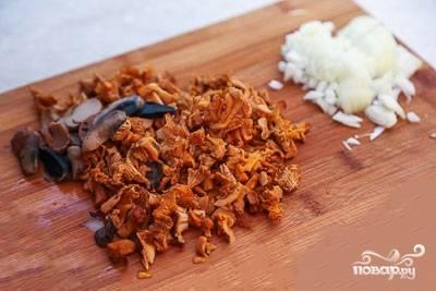 Лисички моем и мелко нарезаем на доске. Так же поступаем с очищенным от шелухи луком. Если грибы были заморожены, то размораживаем их заранее, чтобы стекла жидкость.