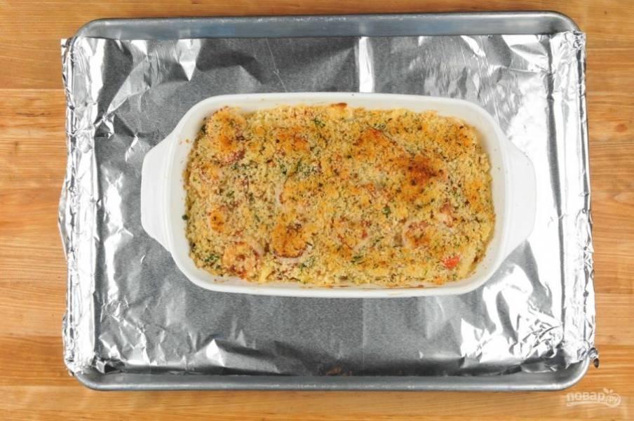 5. В форму для выпечки выложите большую часть пасты. Затем креветки и оставшуюся пасту с соусом. Сверху насыпьте смесь из сухарей.