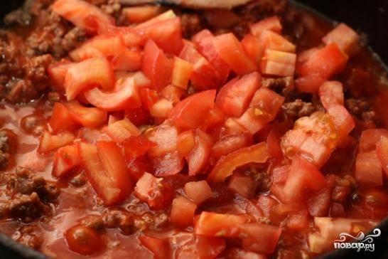 Помидоры необходимо нарезать на небольшие кубики и добавить на сковороду к фаршу. Солим и тушим еще 15-20 минут.
