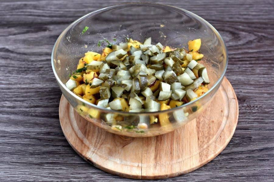 В остывший картофель добавьте соленые огурцы, нарезанные кубиками.