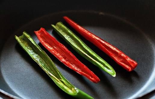 Стручок разрезаем пополам и очищаем от семян, если Вы используете болгарский перец, то нарезаем его длиной соломкой и обжариваем на сухой сковородке на медленном огне около 8 минут.