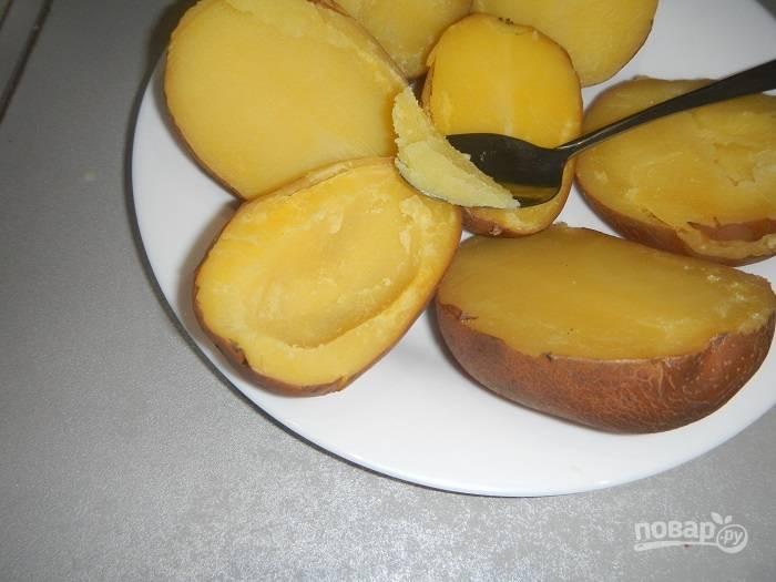 Отварную картошку порежьте пополам и аккуратно удалите мякоть внутри, чтобы остались тонкие стенки (при этом следите, чтобы форма лодочки сохранялась).