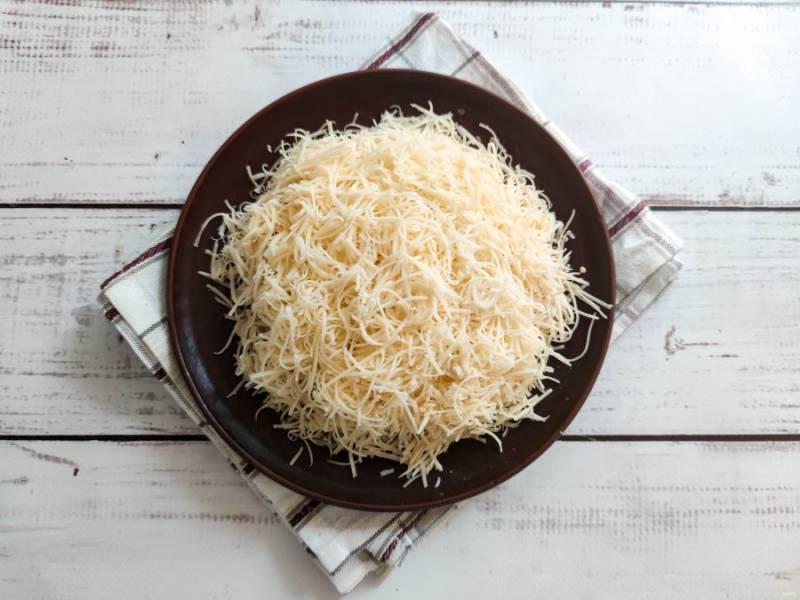 Сверху салат посыпьте мелко тертым сыром.