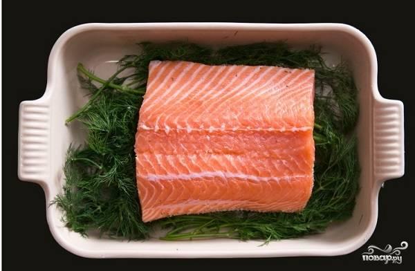 4. Вымойте и обсушите пучок укропа. Половину выложите в форму, в которой будет солиться рыбка. Выложите рыбку на зелень.