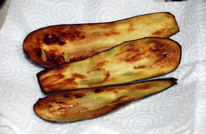 Через пол часа промываем баклажаны под холодной водой, отжимаем их и обжариваем на сковороде до золотистого цвета. Обжаренные пластинки выкладываем на бумажные полотенца, чтобы убрать излишки масла.