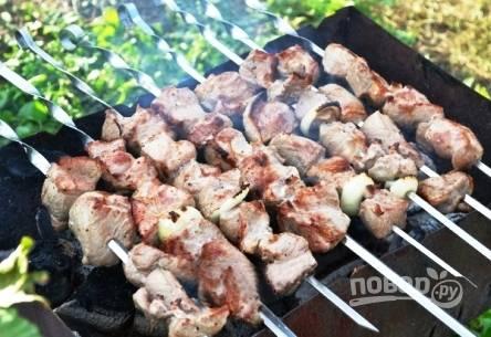 Нанизываем промаринованное мясо на шампуры и жарим до готовности на мангале или в домашней шашлычнице. А готовится такой шашлык очень быстро, так что следите за ним.