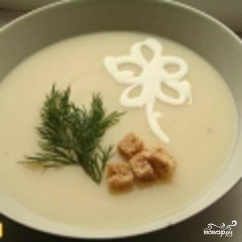 4.Выложить пюре в кастрюлю, добавить воды и вскипятить.  Добавить в суп сметану и тертый сыр. Подогреть 3-4 минуты, пока сыр не расплавится. Хлеб нарезать на маленькие кубики и запечь в духовке до золотистого цвета. При подаче на стол разлейте суп по тарелкам. Сверху положить сухарики и веточку зелени. Приятного аппетита!