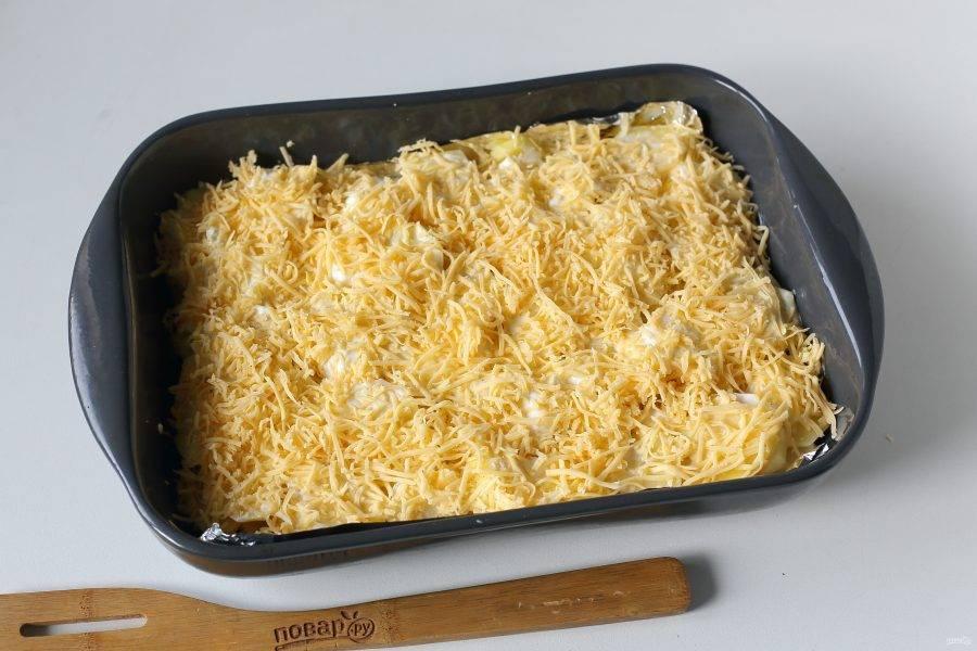 Верх смажьте майонезом и посыпьте тертым сыром.