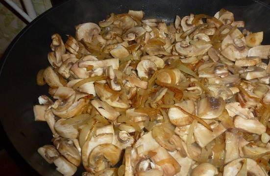 Добавляем к луку грибы и обжариваем, солим и перчим. Затем перемещаем лук и грибы к мясу, готовим вместе 5-10 минут.