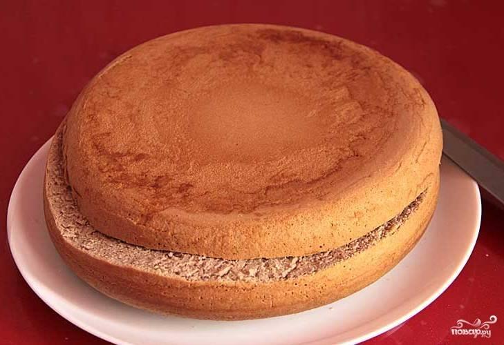 Как только бисквит остынет, начните формировать торт. Разрежьте выпечку вдоль так, чтобы нижняя часть была больше (2 см и 1,5 см). Большую сторону нарежьте на куски по 2,5 см, а меньшую уложите на тарелку для подачи.