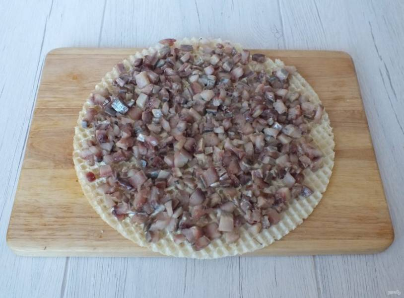 Сельдь разделайте на филе, удалите все кости и нарежьте на средние кусочки. Возьмите вафельный лист, смажьте его небольшим количеством майонеза и разложите подготовленную сельдь.