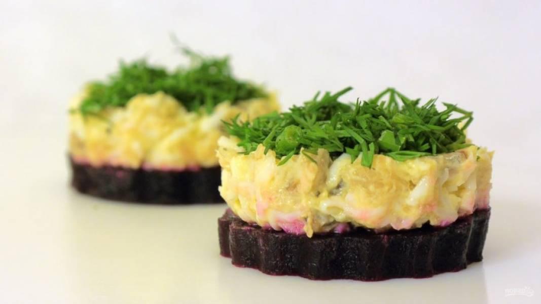 3.  Выложите свеклу на блюдо и с помощью того же стакана или формы выложите на нее начинку, аккуратно ее разровняв. Сверху посыпьте закуску рубленой зеленью. Приятного аппетита!