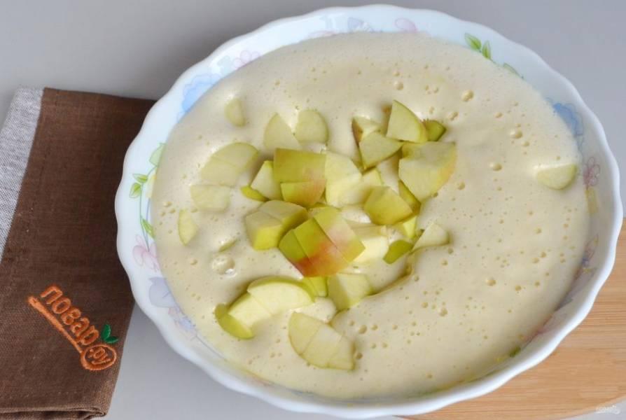 5. Вымойте яблоки, порежьте на четвертинки, удалите сердцевинки. Яблоки порежьте средними кусочками. Положите их в тесто, перемешайте.