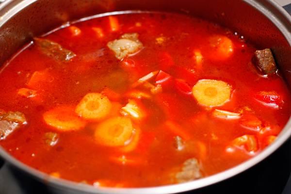 В гуляш добавляем морковь, перец, чеснок, помидоры и заливаем все горячей водой.