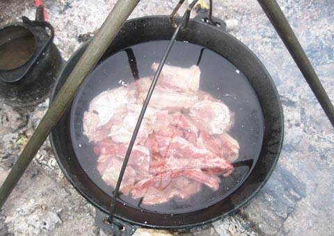 Мясо сложите в казан и залейте водой.